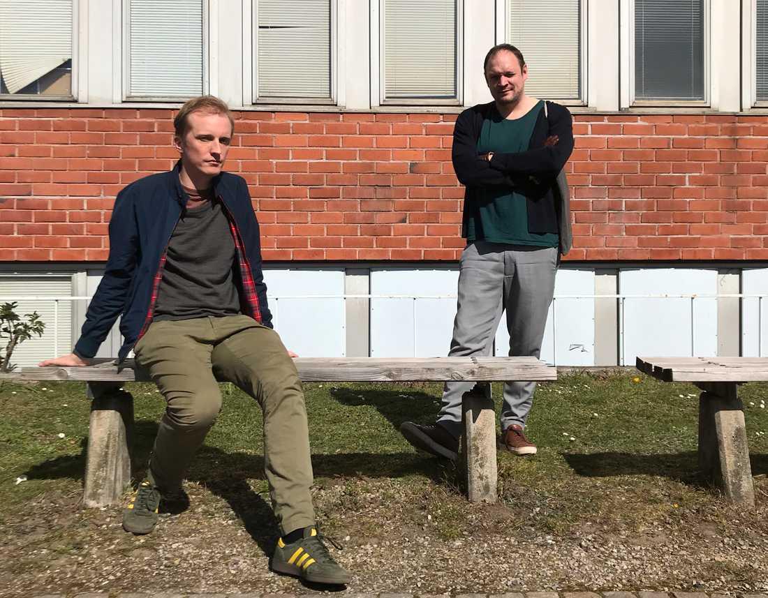 Veckans Stormen-värdar, Ola Söderholm och Jonathan Unge, kopplar av i solen framför en rustik tegelbyggnad.