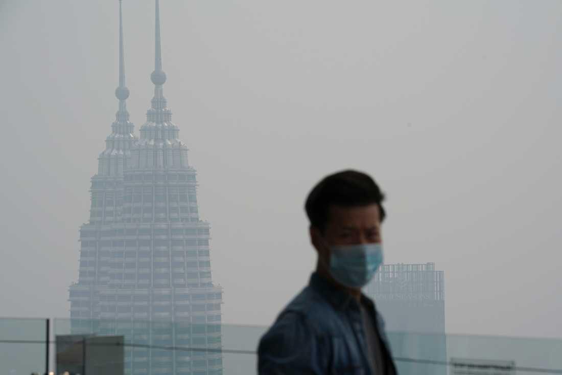 En turist i Kuala Lumpur med munskydd som skydd mot röken som väller in från skogsbränderna i grannlandet.