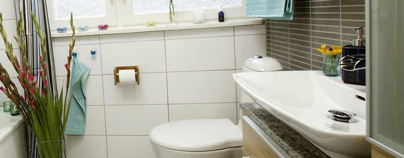 Randigt duschdraperi från Åhléns, 199 kr. I badkaret kan man vila nacken mot Hemtex badkudde, 129 kr. På golvet, som har värmeslingor, ligger en vit badrumsmatta från Hemtex, 199 kr.