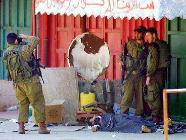 Israeliska soldater fotograferas vid en död palestinier.