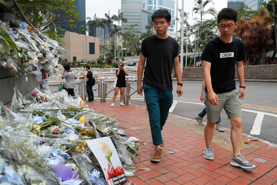 Aktivisten Joshua Wong (till vänster) besöker minnesplatsen för en aktivist som dog efter att ha fallit ned från en byggnad där han satte upp en banderoll.