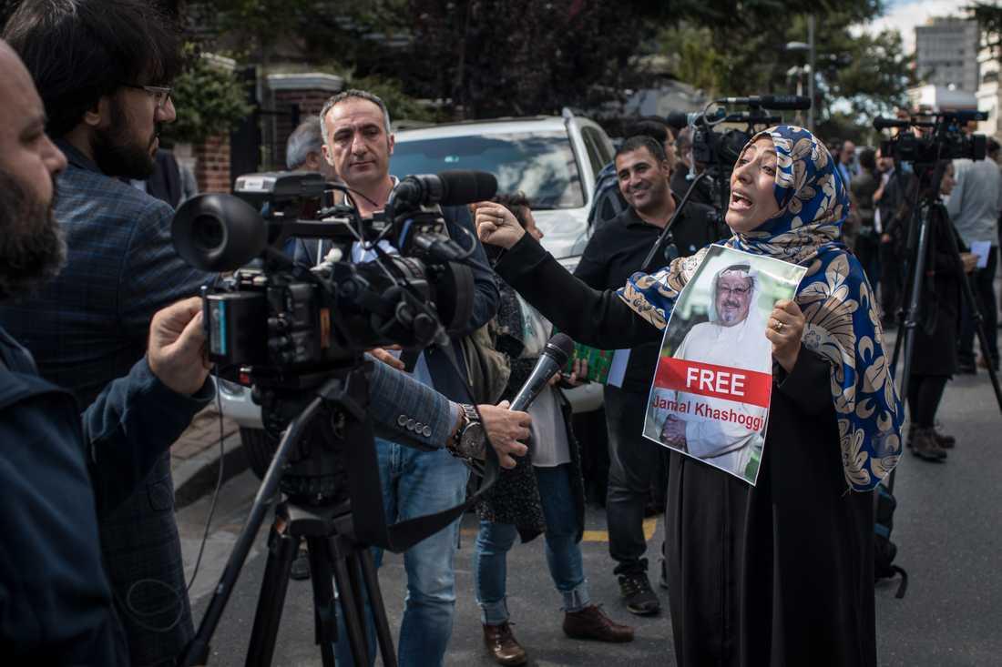 """Nobelpristagerskan Tawakkol Karman håller upp en skylt med orden """"Frige Jamal Khashoggi"""" och hans porträtt framför journalister utanför Saudiarabiens konsulat i Istanbul."""