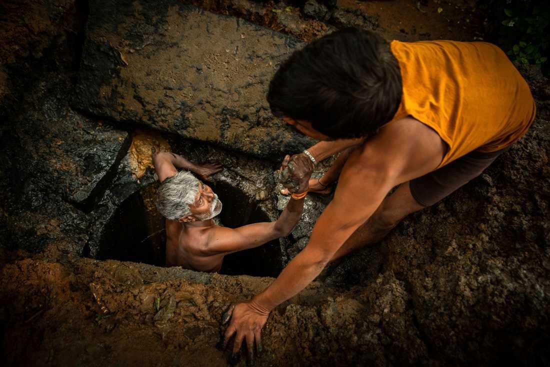 54-årige Kaverappa från Bangalore i Indien hjälps upp ur latrinhålet han håller på att tömma av en kollega. Kaverappa har arbetat som latrintömmare i 35 år.