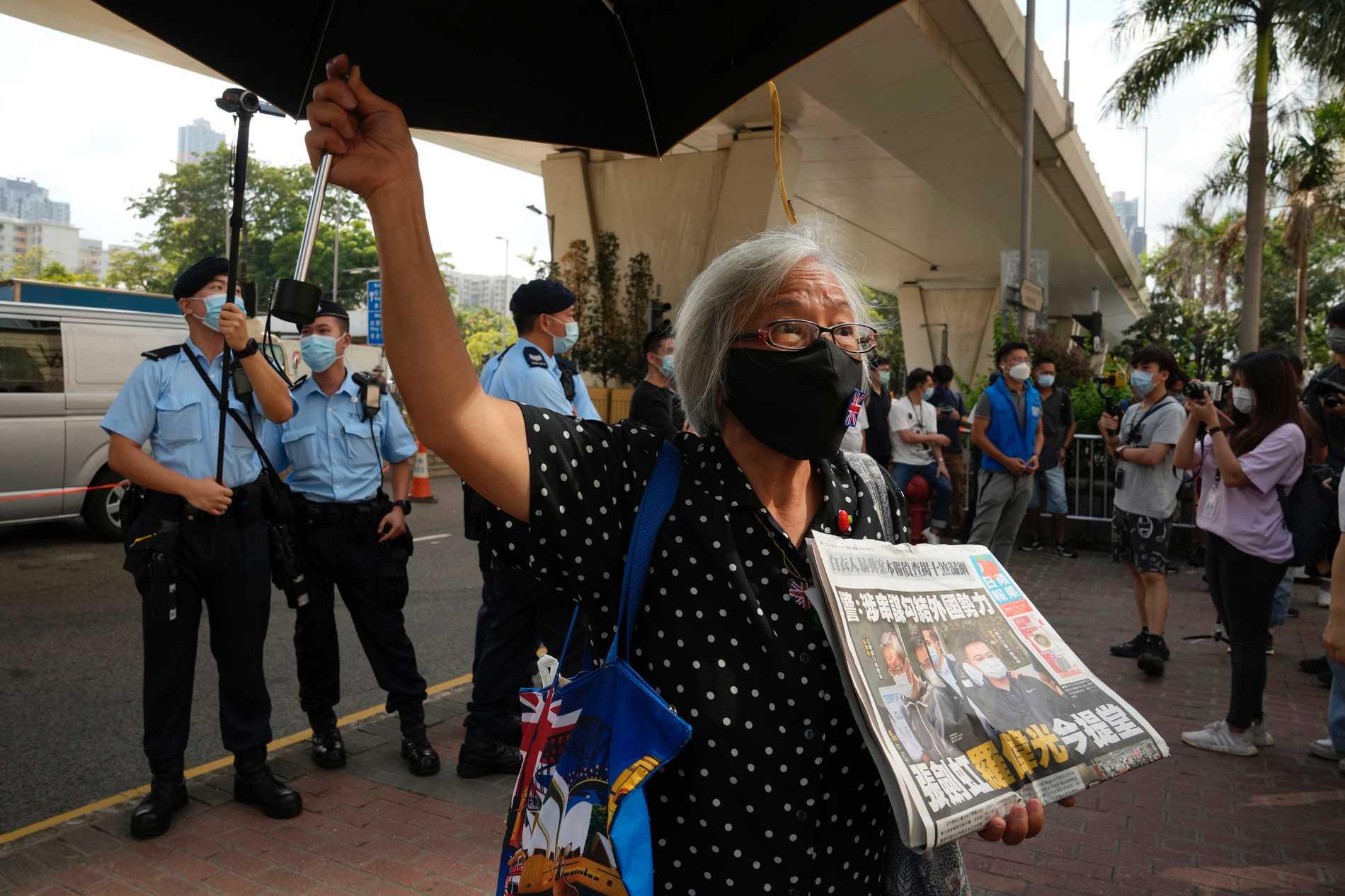 En demokratiaktivist med ett exemplar av Apple Daily utanför en domstol i Hongkong.