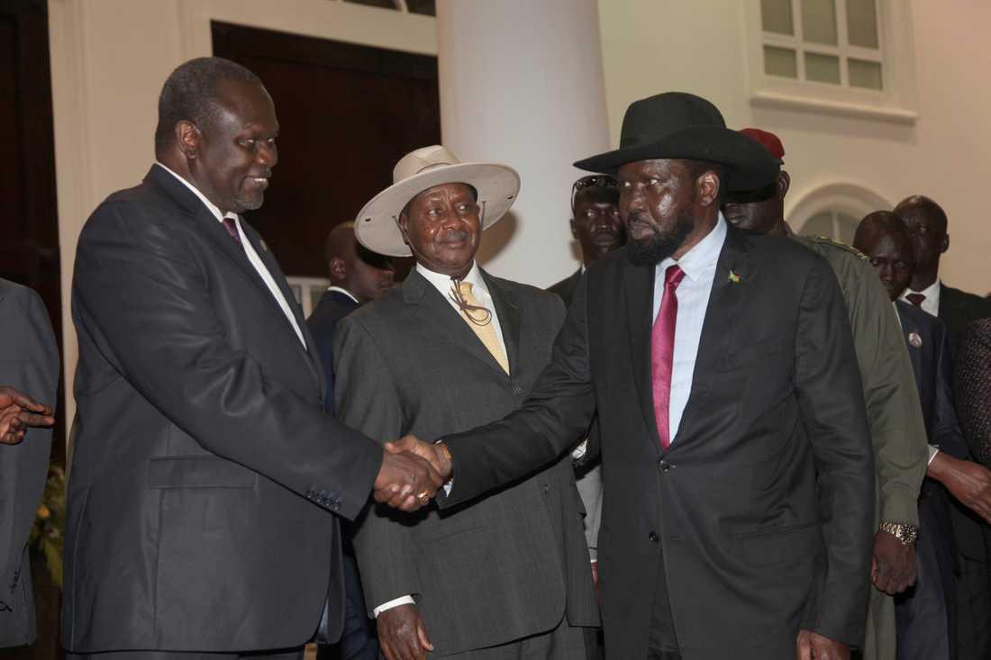 Rebelledaren Riek Machar och Sydsudans president Salva Kiir skakar hand med Ugandas president Yoweri Museveni emellan sig under ett möte i juli. Arkivbild.