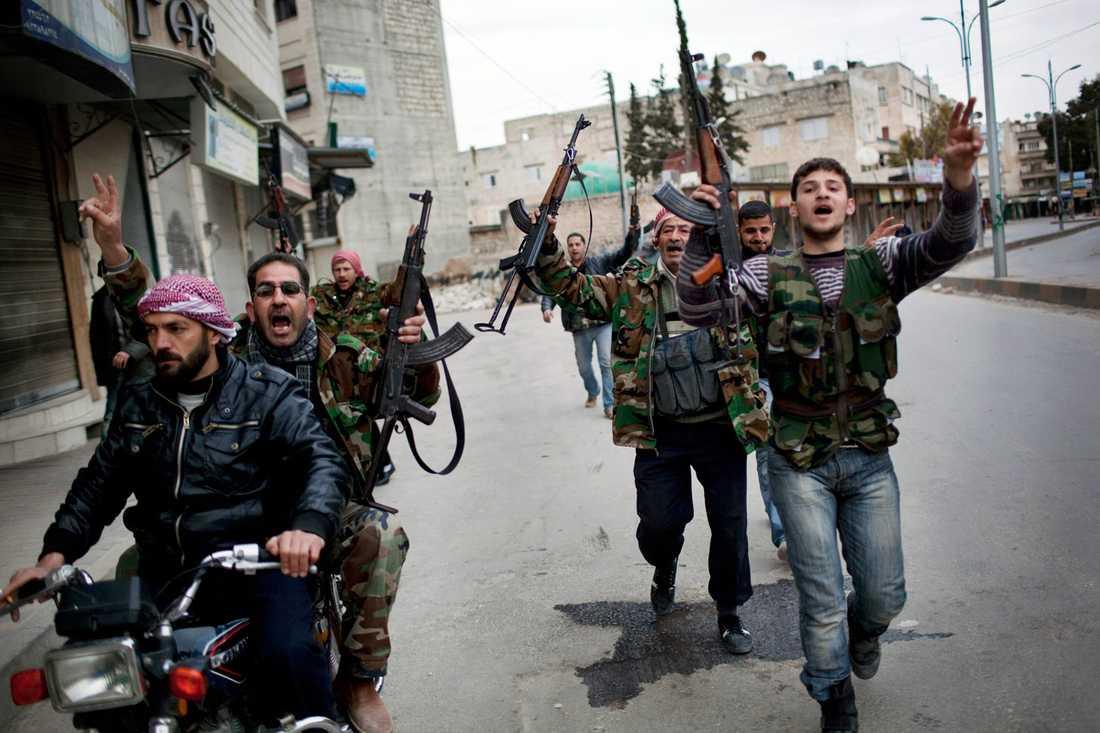 Syriska rebeller firar efter att de fått höra att deras kamrater har förstört en stridsvagn från armén.