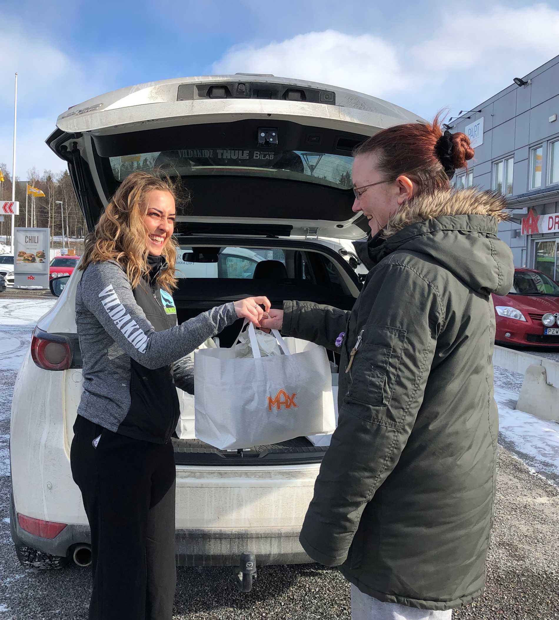 Rebecca Karlsson från föreningen VildaKidz i färd med att räcka över en påse mat.
