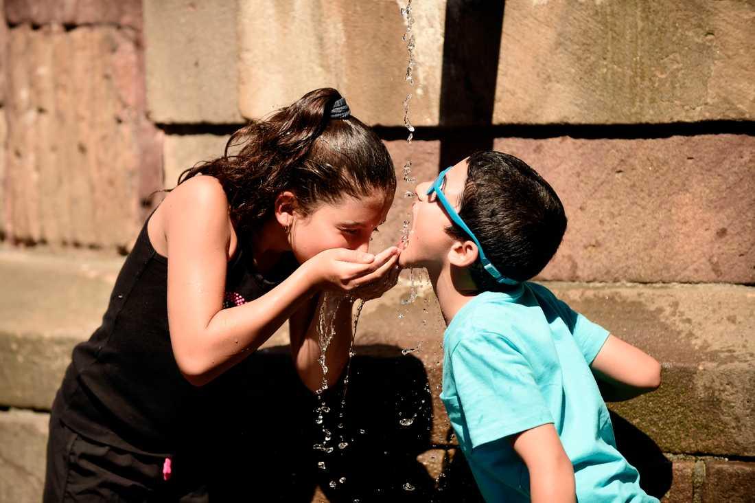 Arkivbild. Två barn dricker vatten ur en fontän i Gamla stan i Stockholm.