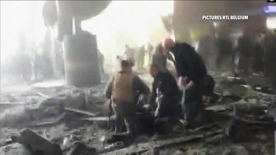 Folk tas omhand efter explosionen på flygplatsen i Bryssel