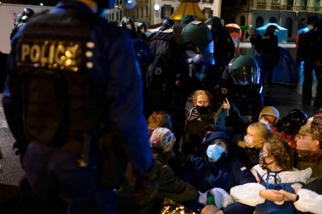 Polis för bort deltagare i klimatprotesten i närheten av den schweiziska parlamentsbyggnaden i Bern.
