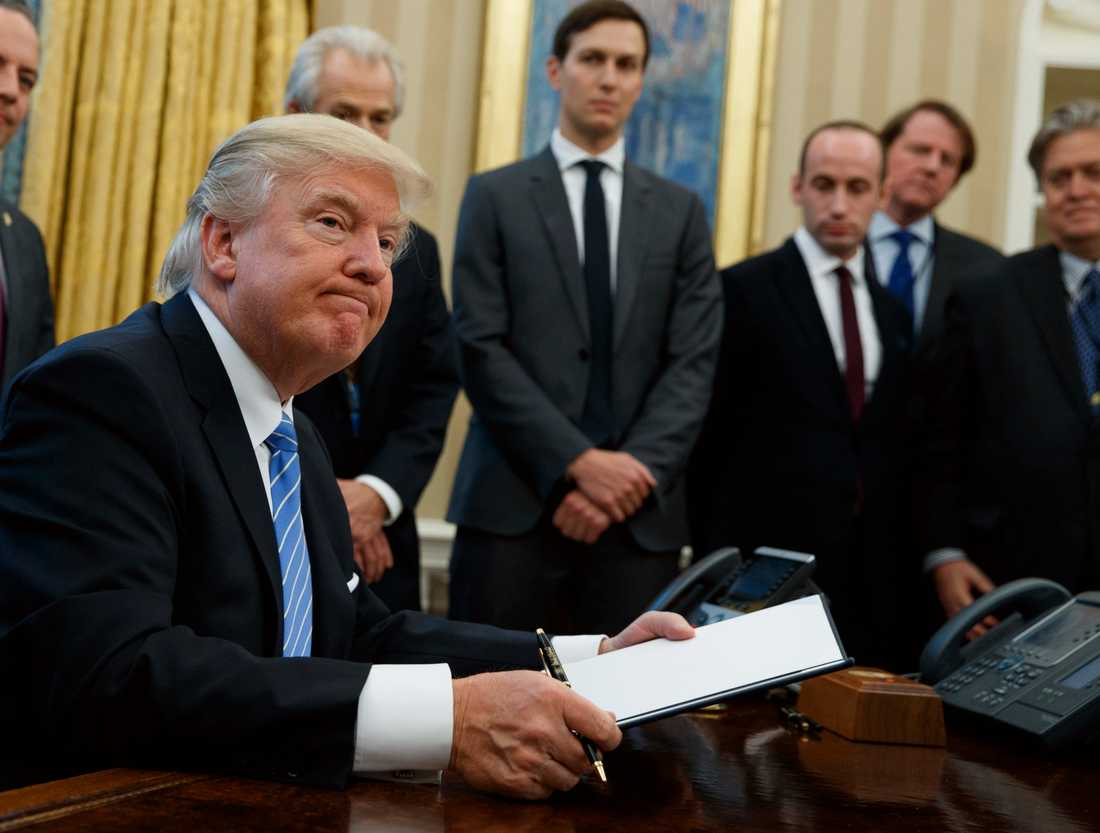 Trump skriver under en presidentorder.