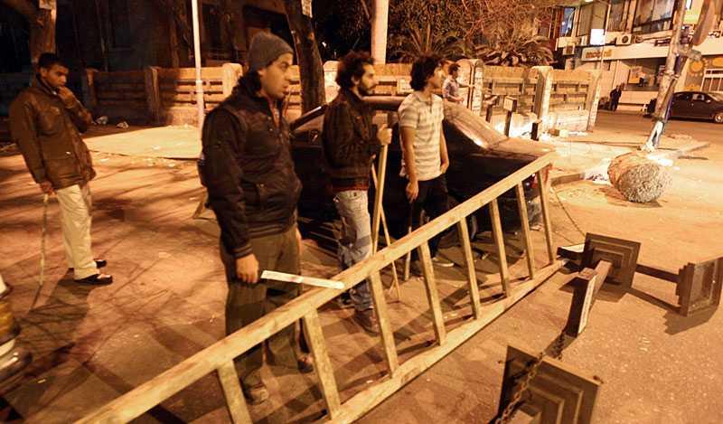 skyddar sig mot länsning I natt höll boende i Kairo vakt vid sina fastigheter. Beväpnade med det som finns till hands bygger de egna barrikader för att hindra plundrarna från att ta det de kan komma över.