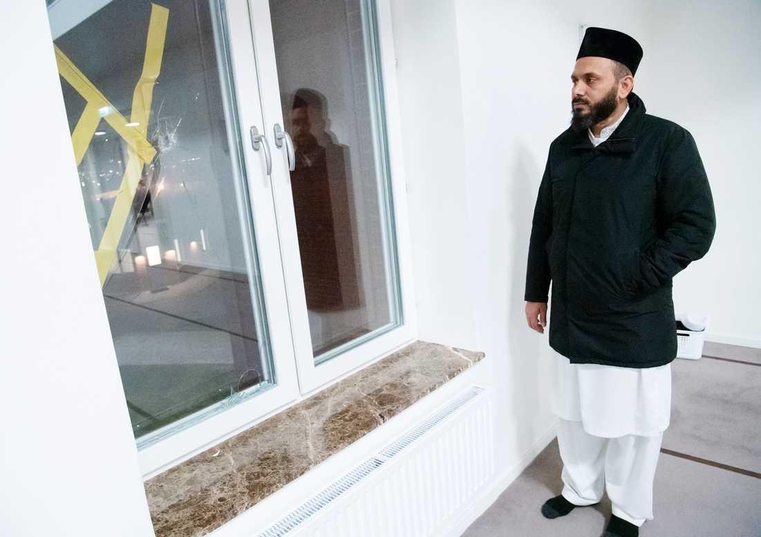 Imam Rizwan Afzal vid skotthålet i ett fönster.