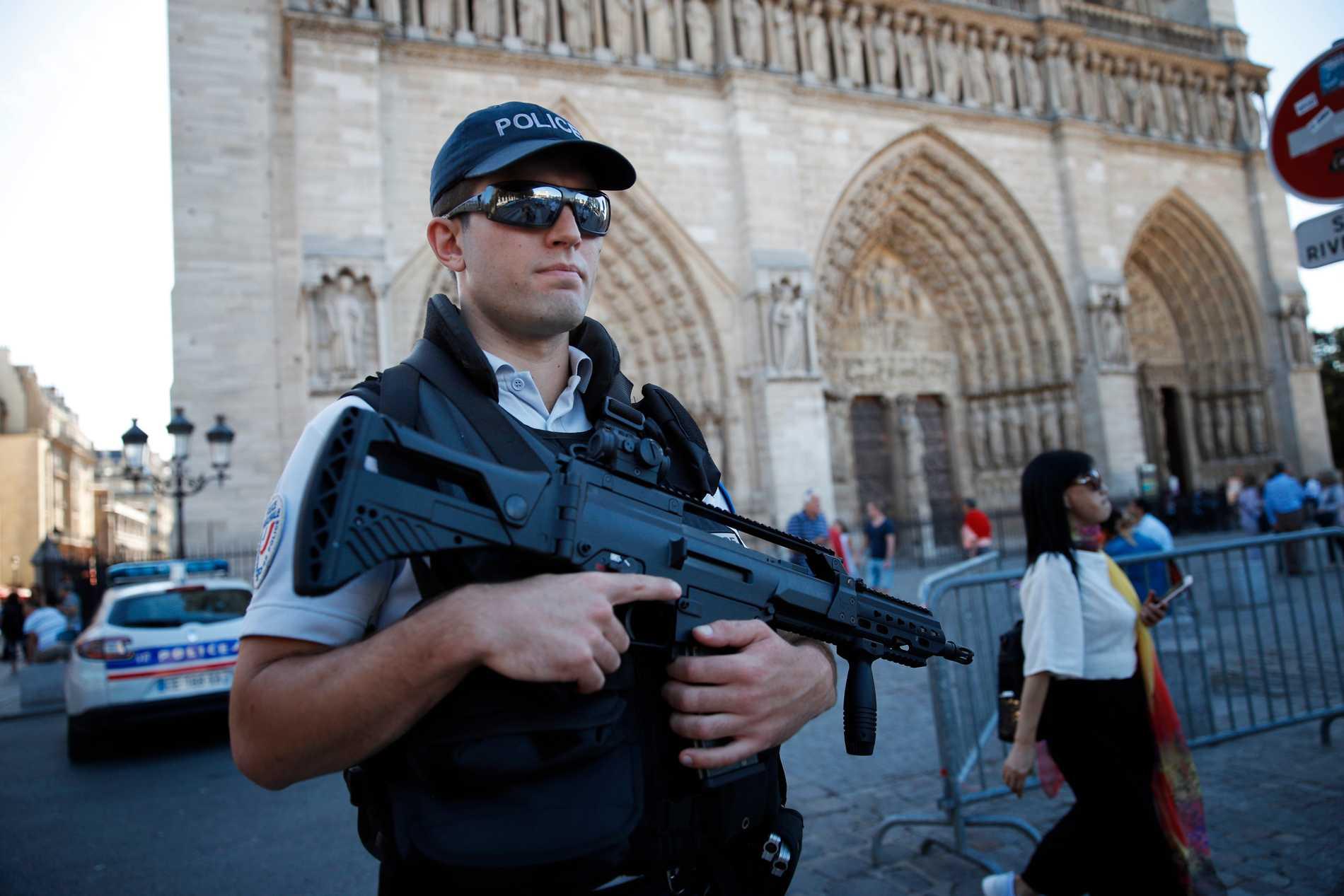 Fransk polis bevakar den då inte eldhärjade katedralen Notre-Dame i Paris 2016.