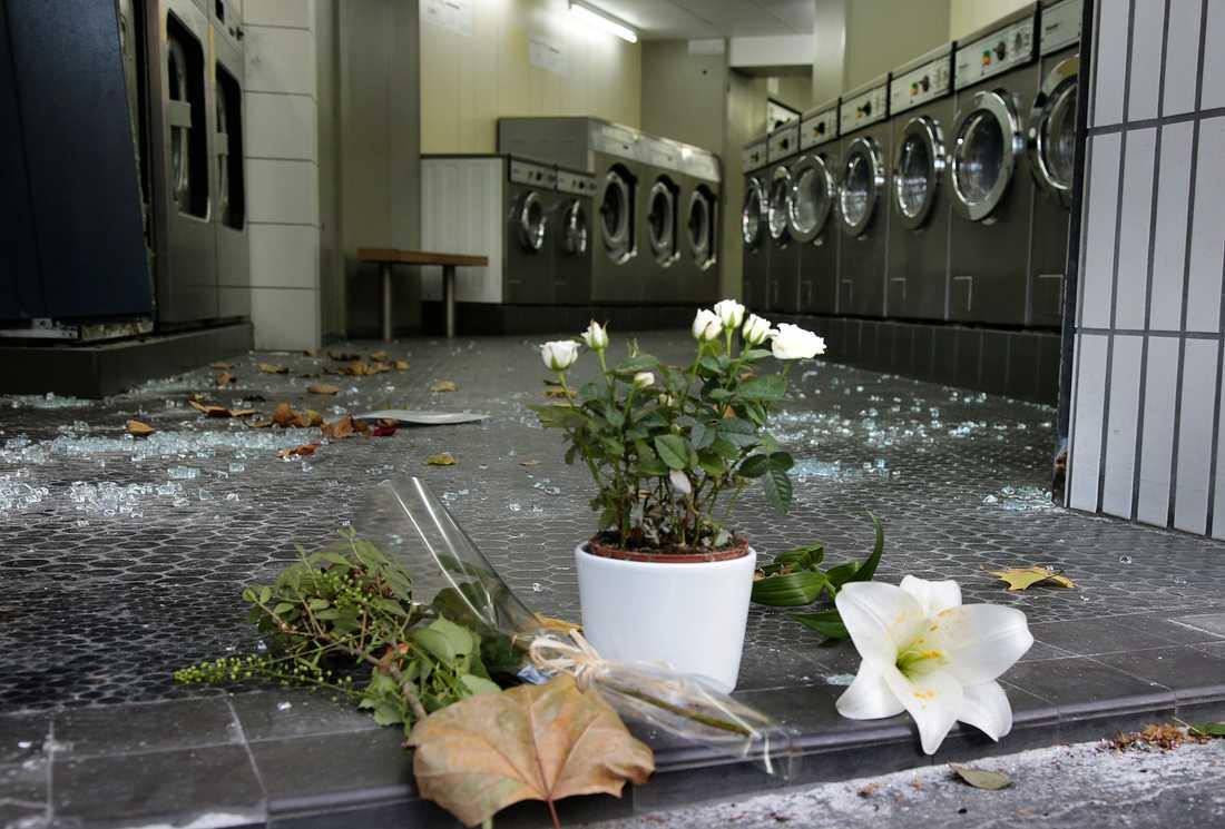 Blommor och glassplitter kantar en tvättinrättning i närheten av en av platserna för attackerna.