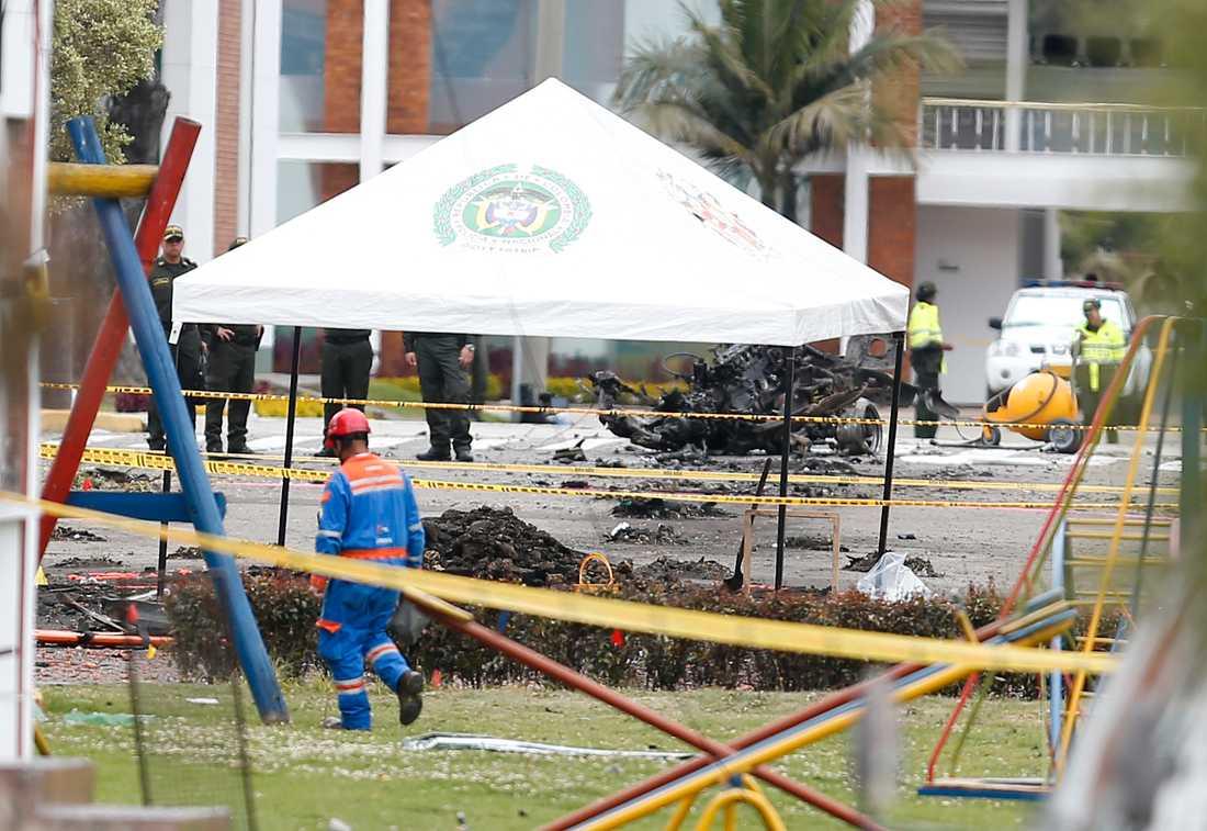 Poliser undersöker platsen där gärningsmannen detonerade en sprängladdning under en promoveringsceremoni för nya poliskadetter i Bogotá i torsdags.