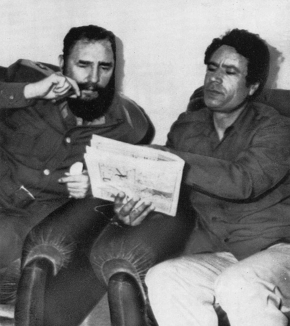 Kubas ledare Fidel Castro och Gaddafi studerar nyheterna i tidningen tillsammans.