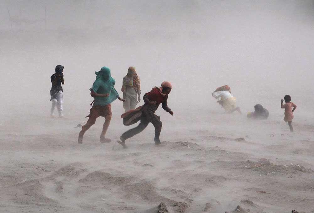 En grupp människor kämpar mot en storm i den pakistanska staden Lahore. Kraftiga oväder satte stora delar av trafiken i staden ur spel på söndagen.