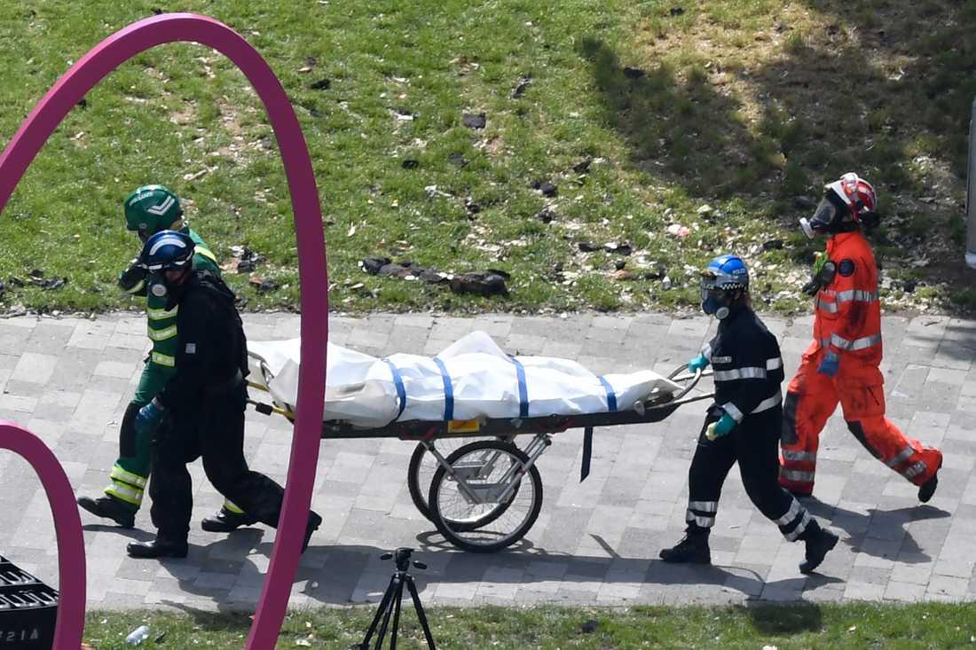 Räddningstjänster bär iväg en kropp från huset på fredagen.