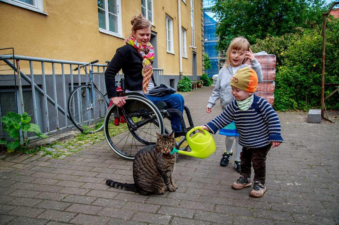"""Otto, 1,5, försöker """"vattna"""" katten på gården i Malmö. När Anna Oredsson, 34, blev gravid med Maja, 4, fanns ingen kunskap i vården om  ryggmärgsskada, graviditet och förlossning"""