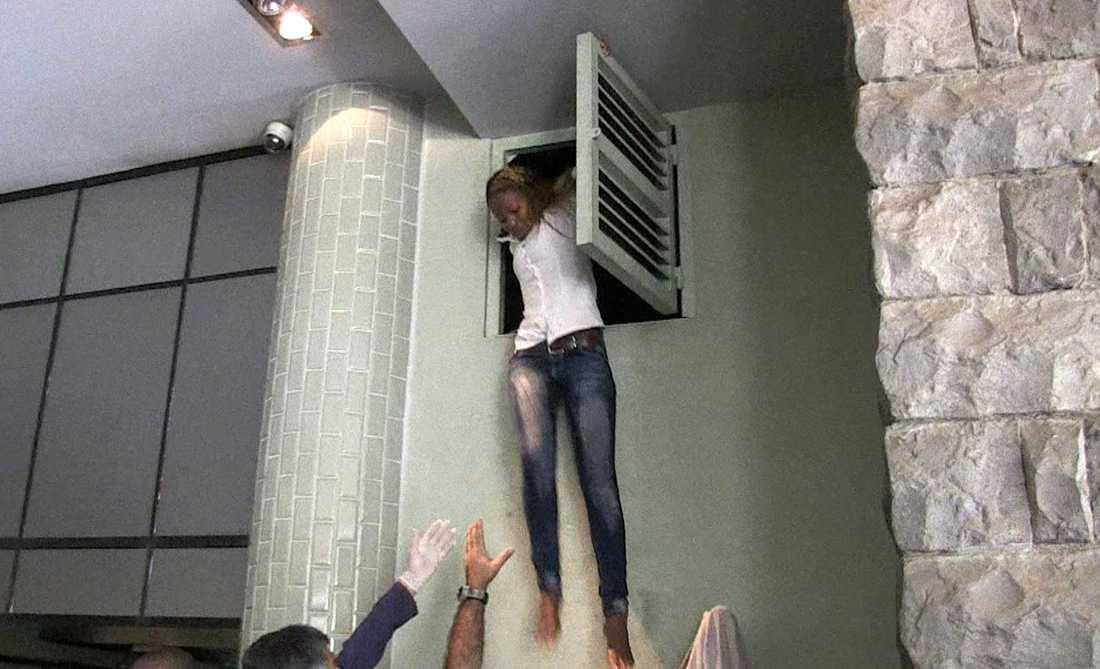 En kvinna kommer ut från ett ventilationsrör där hon gömt sig under attacken.