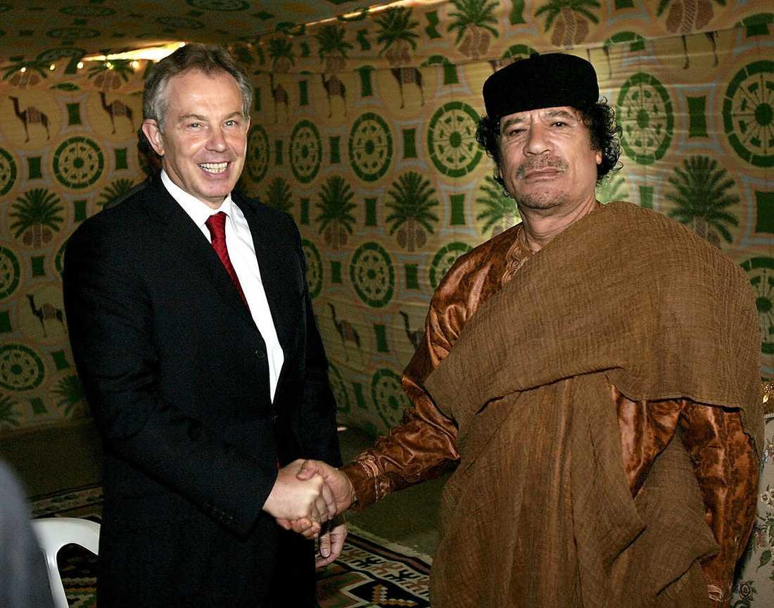 Skakar hand med Storbritanniens dåvarande premiärminister Tony Blair.