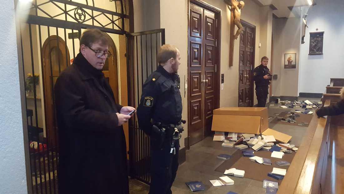 Kyrkoherde Tobias Unnerstål (tv) i samtal med polisen sedan Katolska kyrkan i Göteborg utsatt för vandalism. Bland annat har psalmböcker har vräkts ut över golvet.