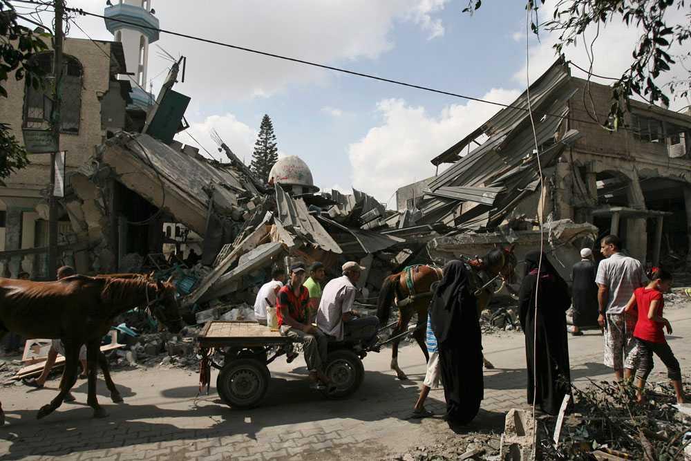 Palestinier vid Al Farouk-moskén, en av flera som förstörts i attackerna.