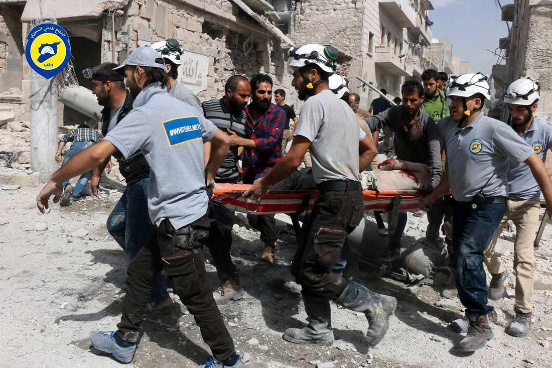 Vita hjälmarna transporterar en skadad till sjukhus. AFP PHOTO / THAER MOHAMMED / TT