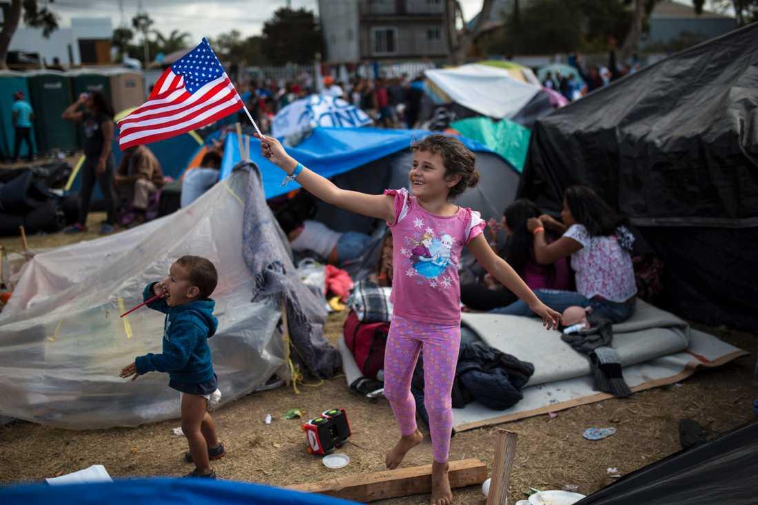En sjuåring från Honduras viftar med USA:s flagga i ett läger för centralamerikanska migranter i Tijuana, Mexiko.