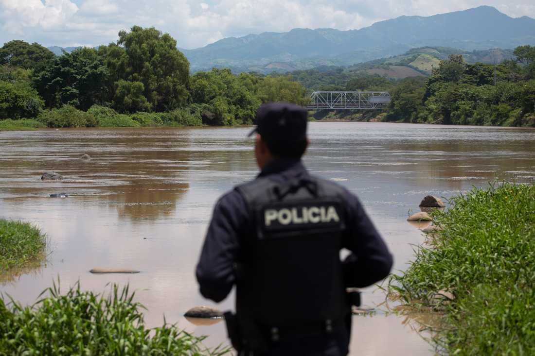 En polis i El Salvador ser ut över en flod vid gränsen mot Guatemala. Arkivbild.