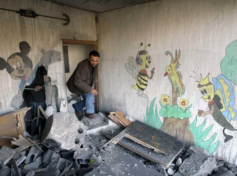 En man inspekterar skadorna på en barnklinik som träffats av en israelisk raket på söndagsmorgonen.