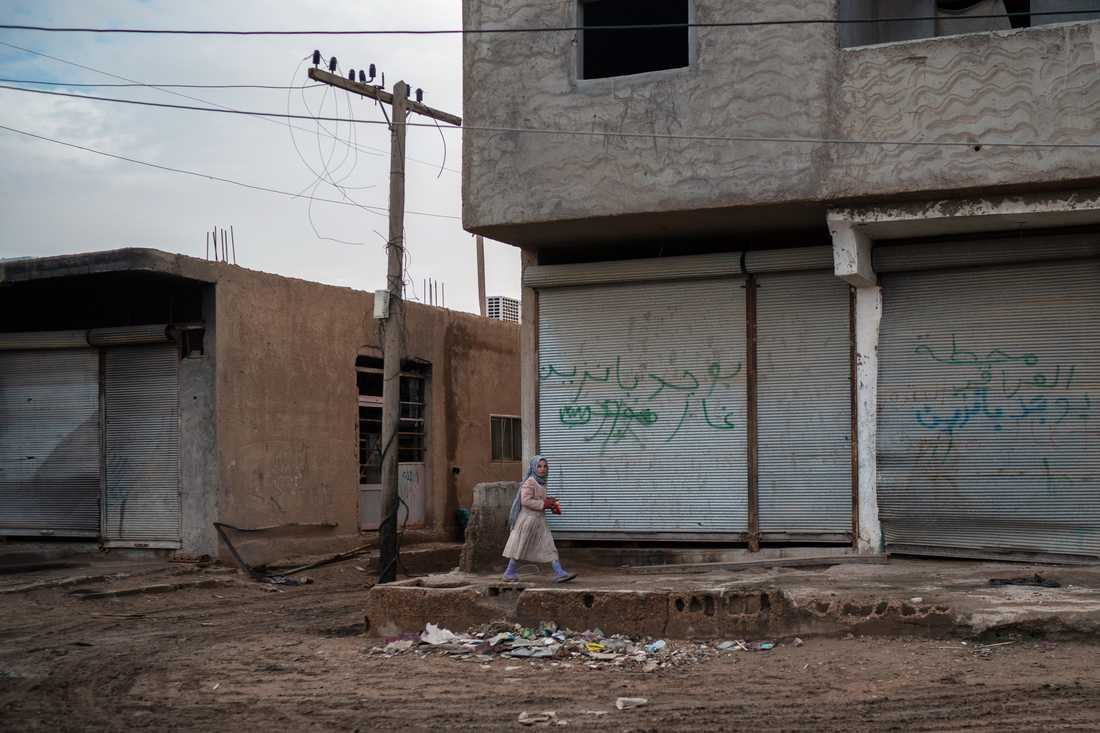 En flicka går förbi i ett område i staden Hajin i östra Syrien, några veckor efter att staden återtagits från terrorgruppen IS i en offensiv som enligt FN:s utredare skördade många civila dödsoffer.