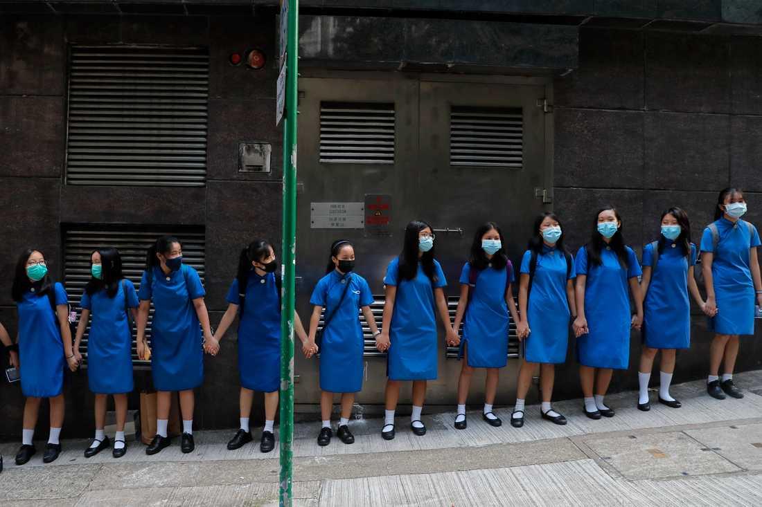 Maskerade studenter håller varandra i händerna vid S:t Stephens Girls' College i Hongkong.