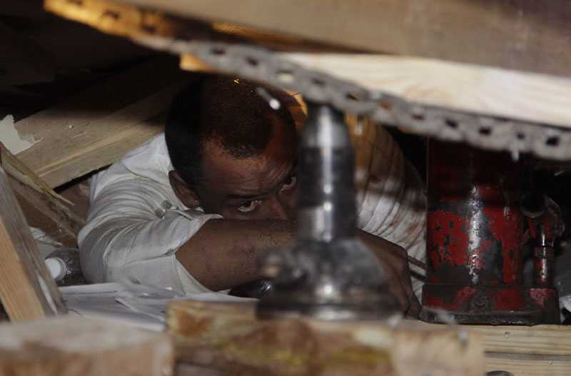 fånge under betongen En man som ligger fångad under ett kollapsat hus ser hjälpen komma. Räddningsteamet försöker palla upp betongplattorna för att kunna få ut honom.
