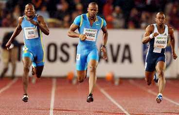 Trots regnet var Jamaicanen Asafa Powell (mitten) 7 hundradelar från världsrekodet på 100 meter.