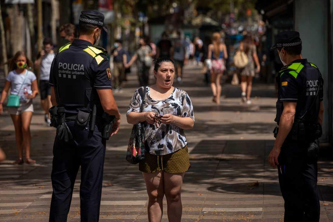 Katalansk polis säger till en kvinna att det är obligatoriskt att bära munskydd. Arkivbild.