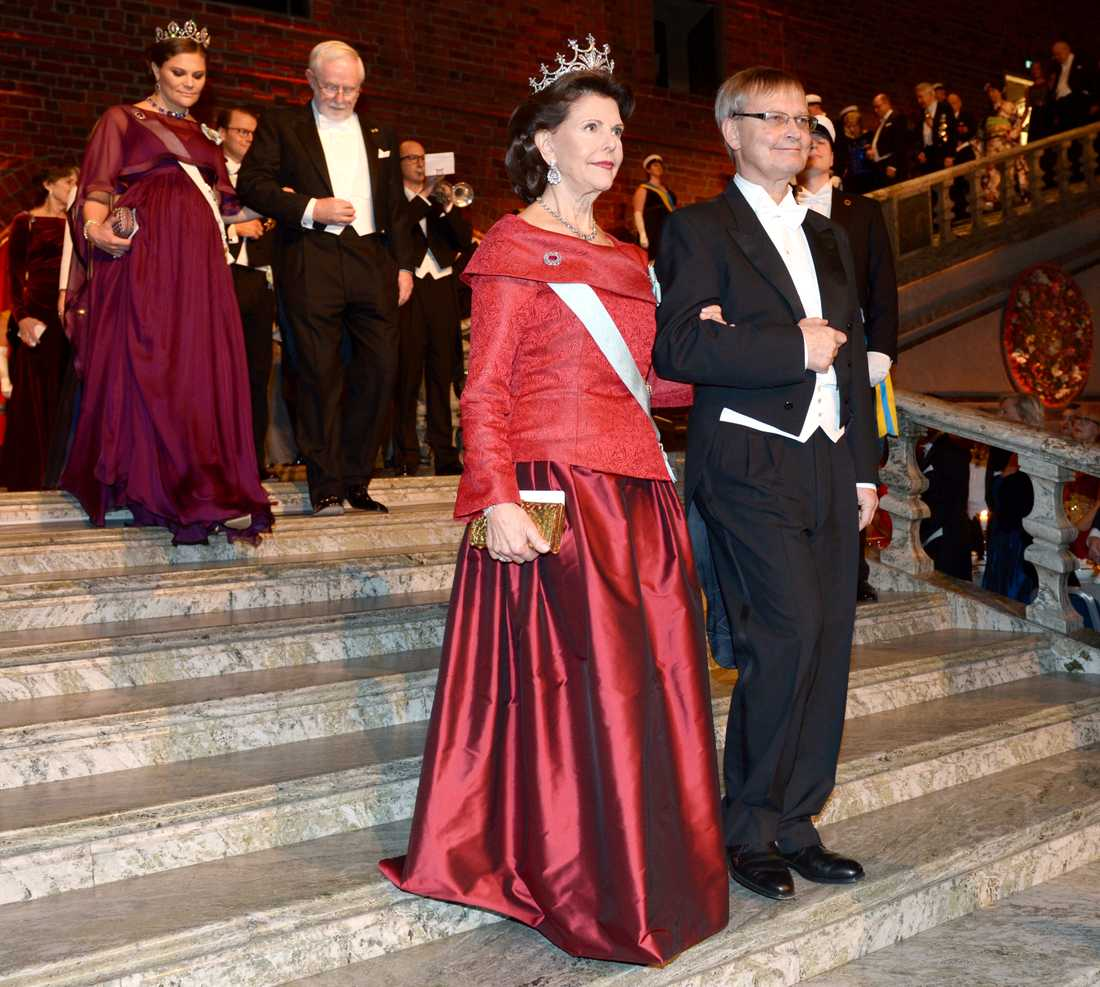 Drottning Silvia och Carl-Henrik Heldin, ordförande för Nobelkommittén, anländer till Blå hallen inför Nobelbanketten i Stadshuset i Stockholm på torsdagen.