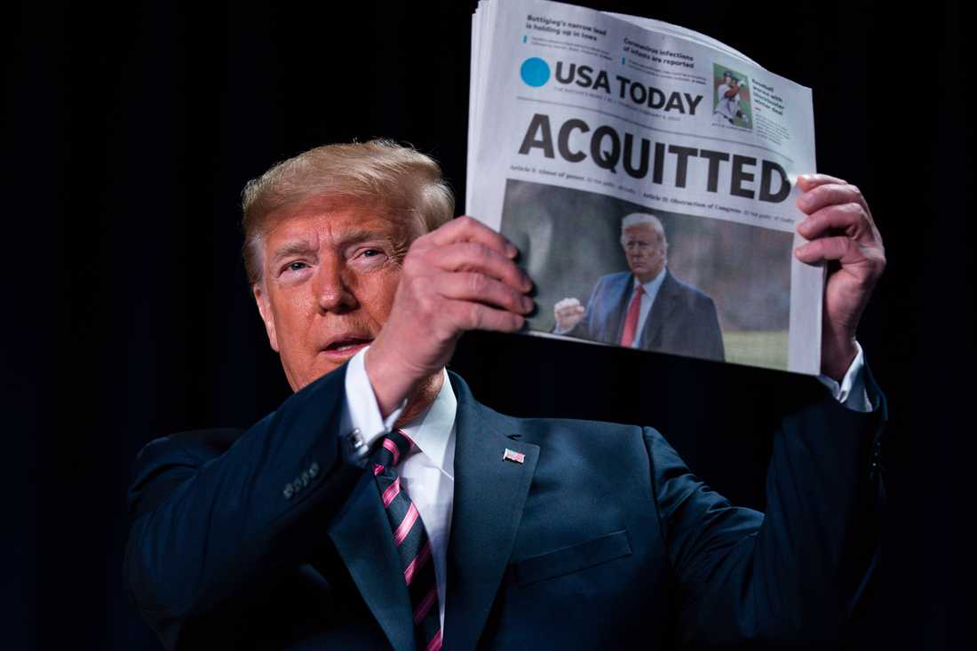 """USA:s president håller upp en tidning med rubriken: """"Frikänd""""."""