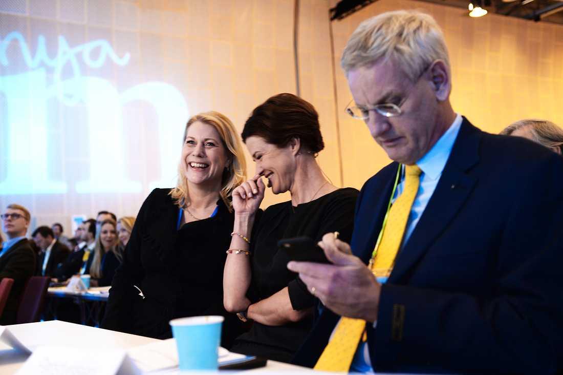 Karin Elmsäter Svärd i samspråk med Anna Kinberg Batra under avgående partiledaren Fredrik Reinfeldt tal. Carl Bildt kollar sin telefon.