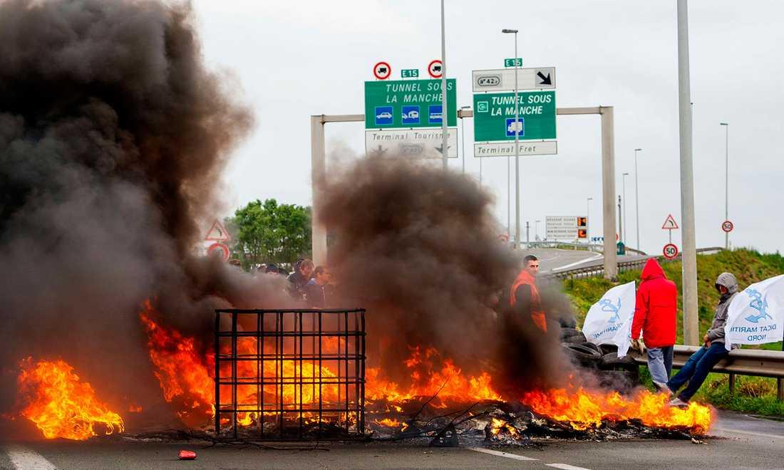 Strejkande färjearbetare har tänt eld på bildäck.