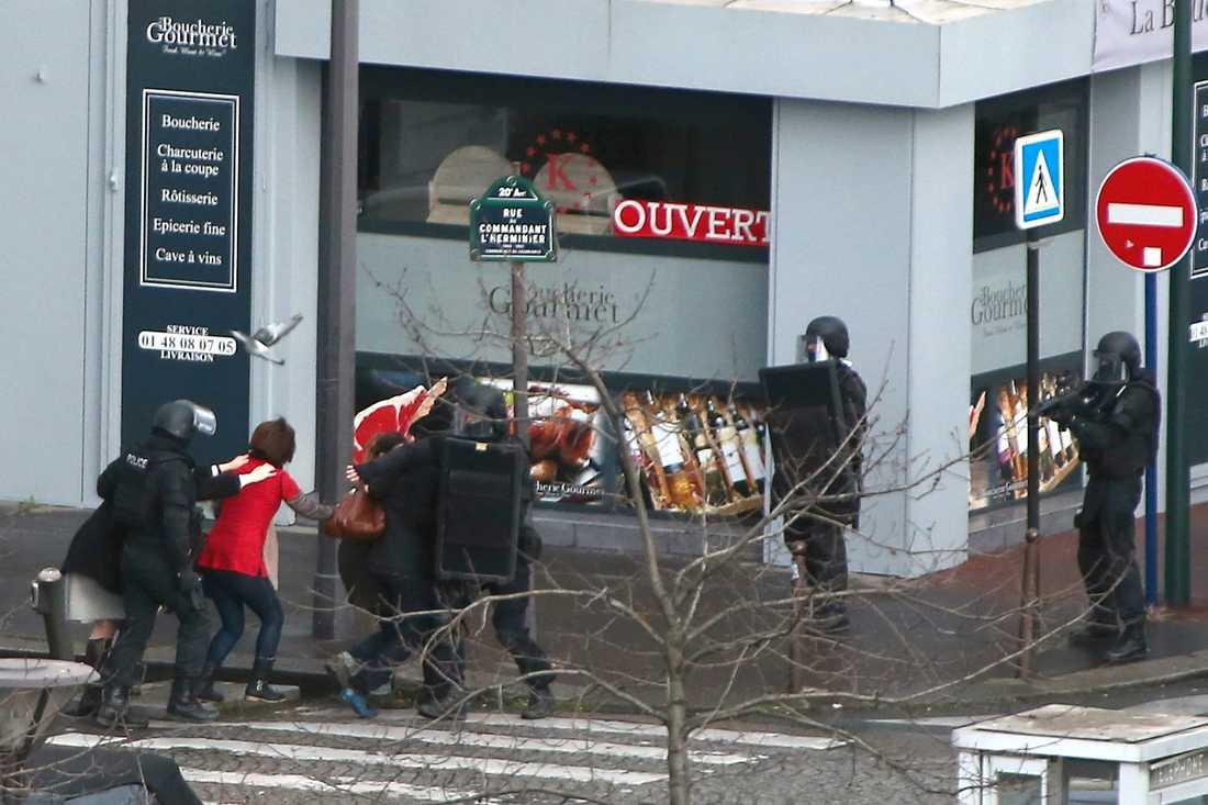 Civila evakueras kring butikdör gisslan befinner sig