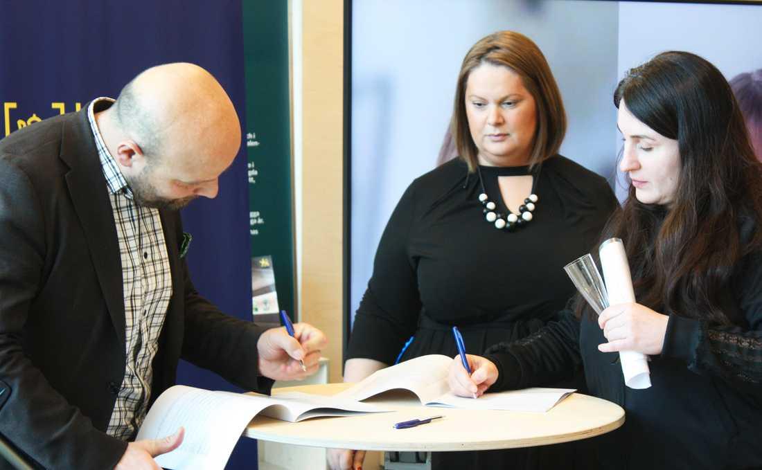 Mohamad Hassan (L), Eva Christiernin (S) och Talin Davidian, ordförande TRIS, signerar överenskommelsen.