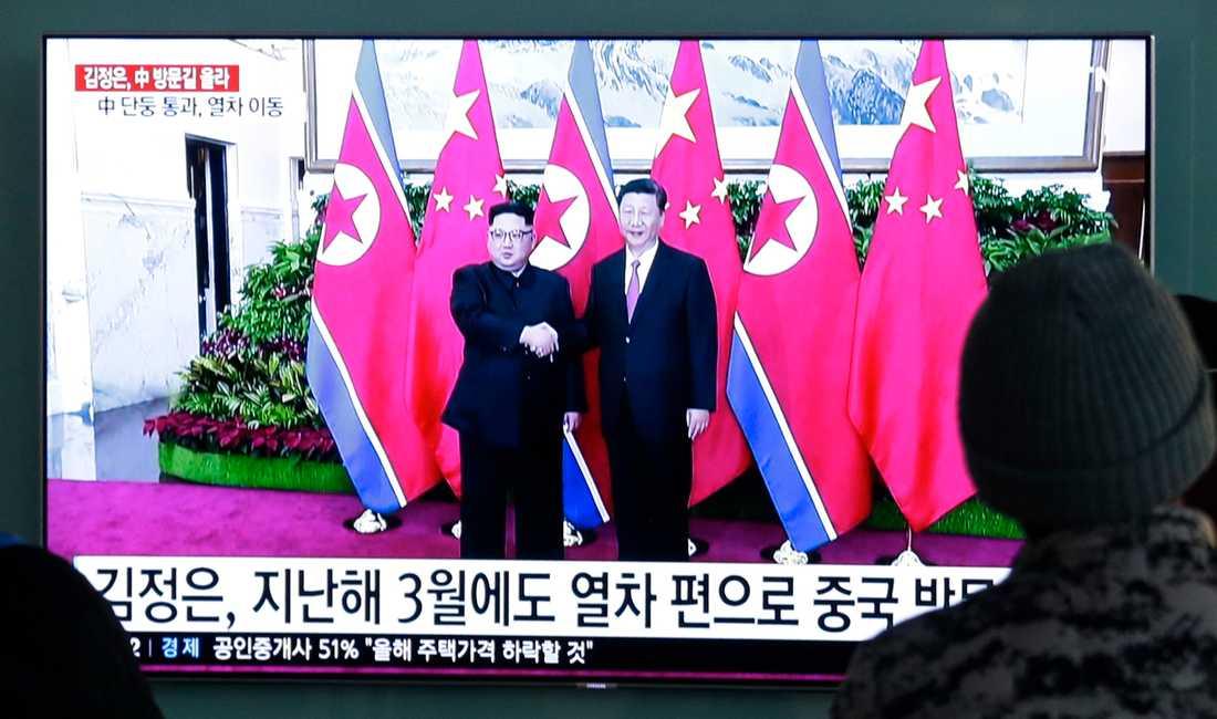 Arkivbilder från ett tidigare möte mellan Nordkoreas ledare Kim Jong-Un och Kinas president Xi Jingping visas på tv i Seoul i samband med Kim Jong-Uns resa till Peking.