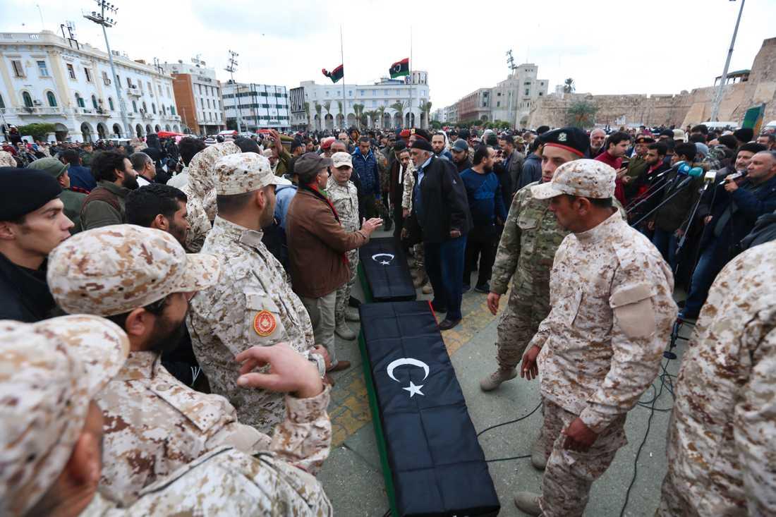 Soldater står vid kistorna i samband med begravningen av några av de kadetter som dödades i en attack i Tripoli tidigare i år. Arkivbild.