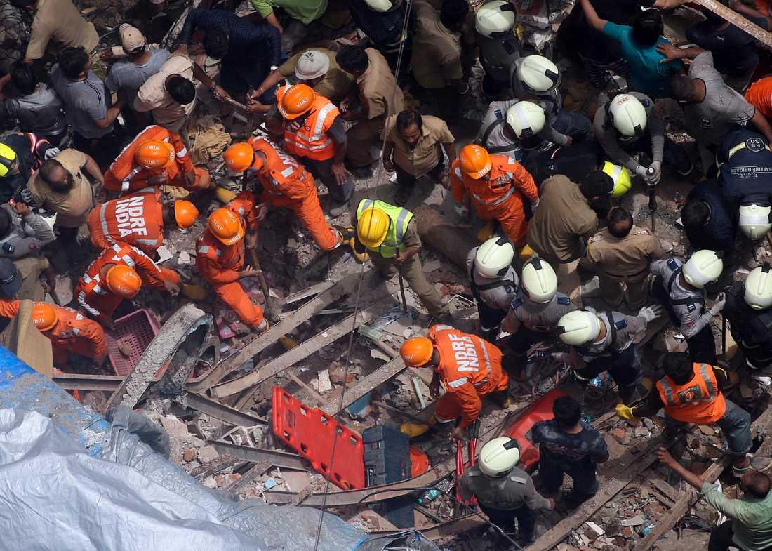 Räddningsarbetare vid det rasade huset i Bombay.