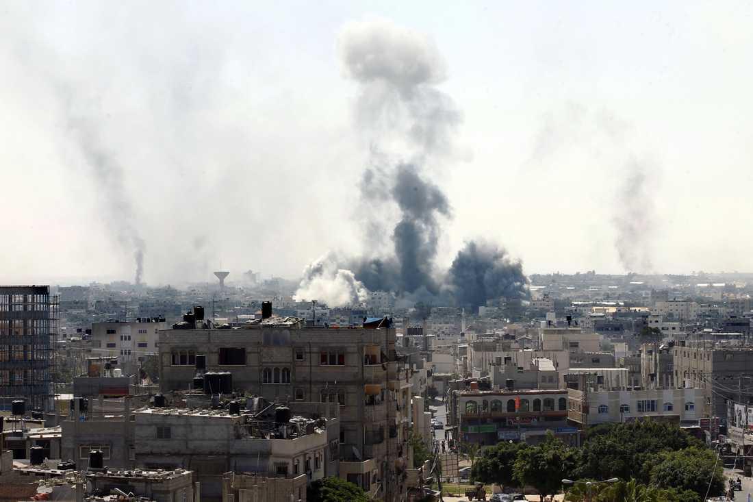 Rök syns från byggnader som träffats under ett israeliskt anfall på fredagen.