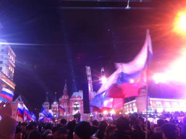 Vilt firande I centrala Moskva firar tusentals Putin-anhängare med flaggor och plakat.