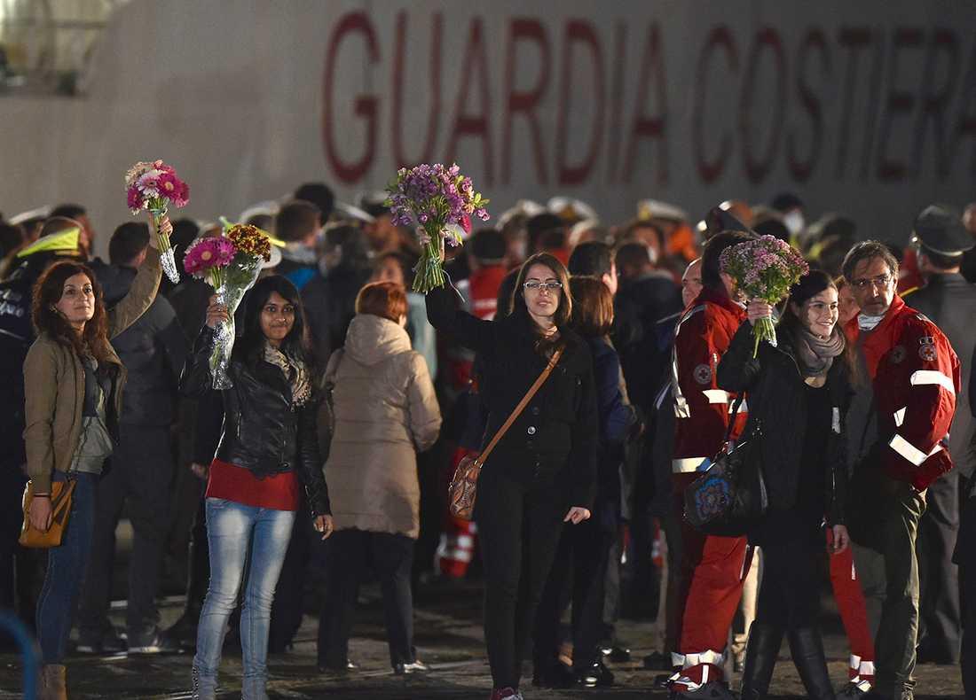 Människorättsaktivister håller blommor i hamnen.