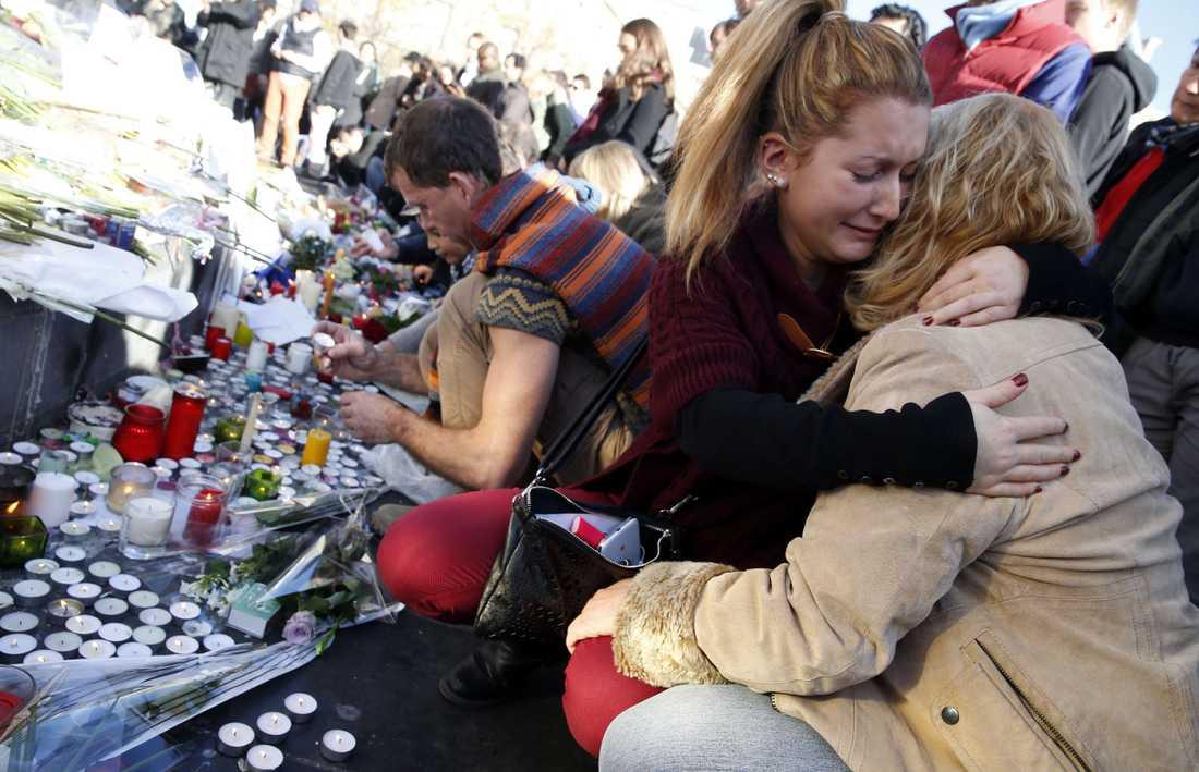 Parisare tröstar varandra vid Monument a la Republique.